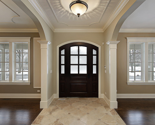 Foyer with arched mahogany door, new construction